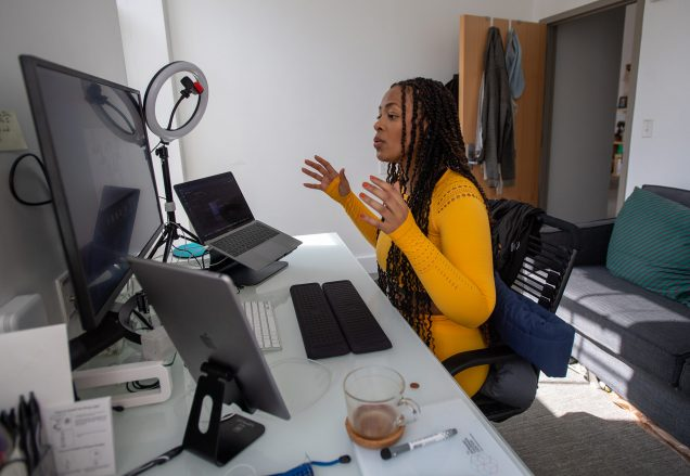 "Photo of Saida Grundy, a CAS assistant professor of sociology, teaching her Race, Class and Gender course from the ""cockpit"" in her home September 29. She wears a bright orange outfit and speaks to her students on screen."