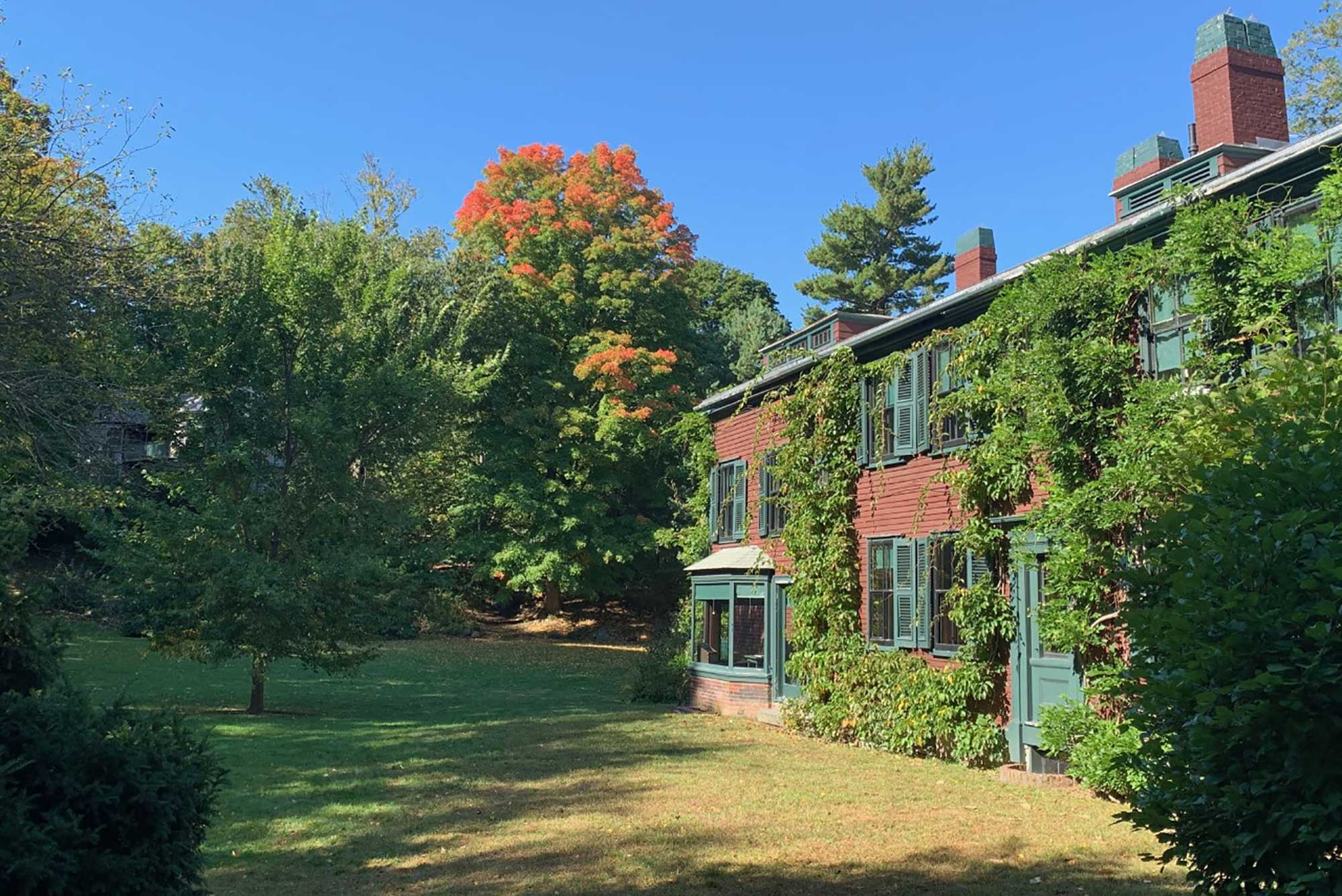 Photo of the old home of Frederick Law Olmsted in Brookline. The leaves on the trees behind the crimson-colored house are starting to turn.