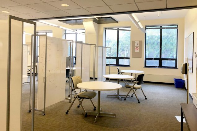 Photo of room 302 at 730 Commonwealth Ave, circular tables with single chairs are in a row divided by white boards. This space is now reservable using a new student study app.