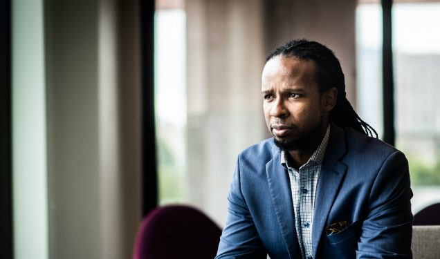 Photo of Ibram X. Kendi sitting in a blue suit looking out a window.