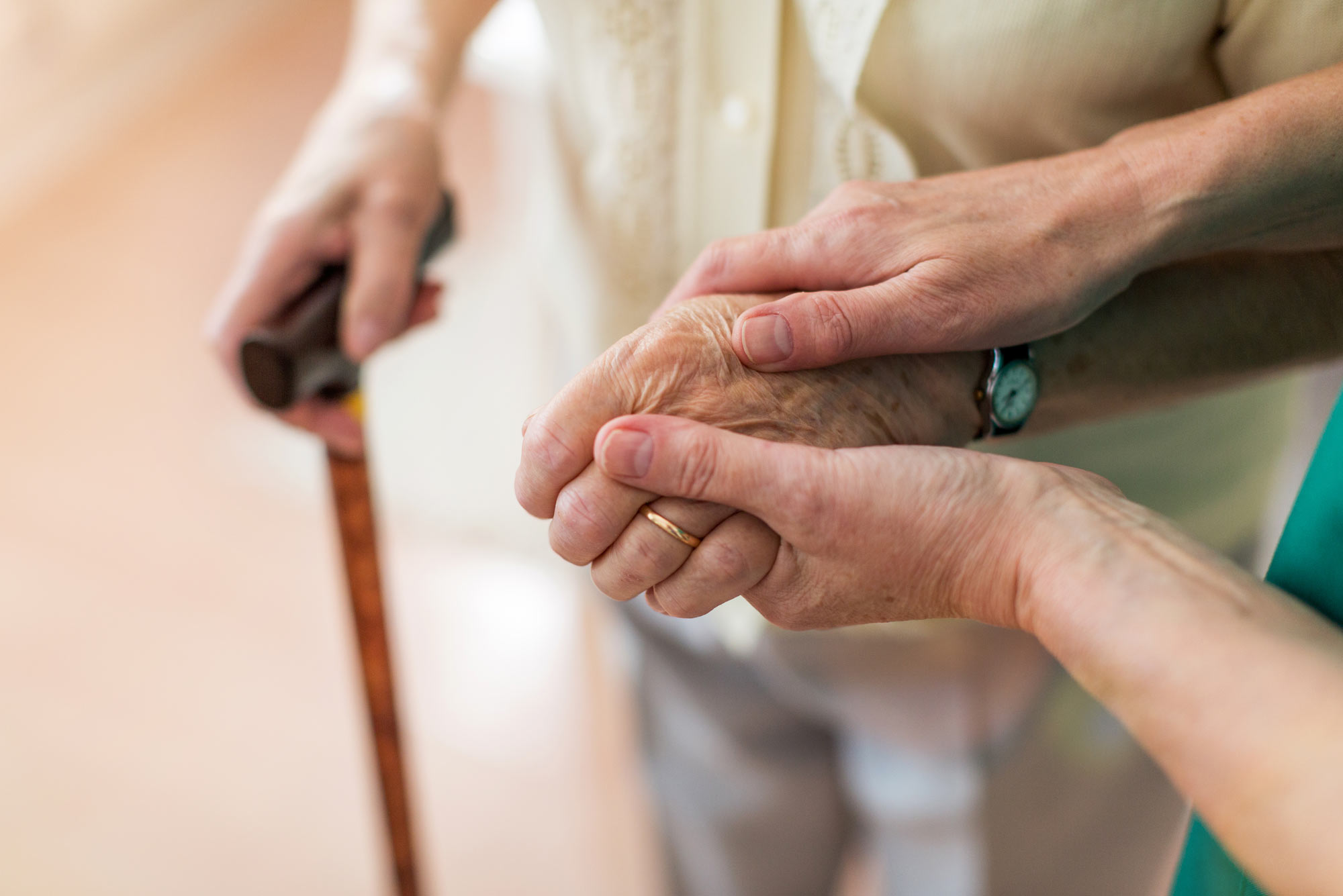 A photo of person holding another person's hand as the use a cane