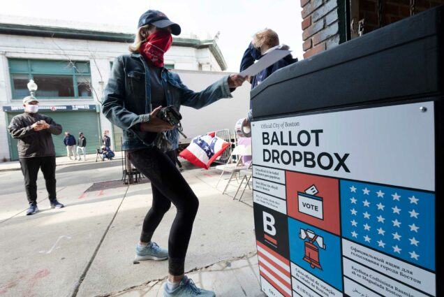 A woman places her ballot in a dropbox after voting at Fenway Park, Saturday, Oct. 17, 2020, in Boston.