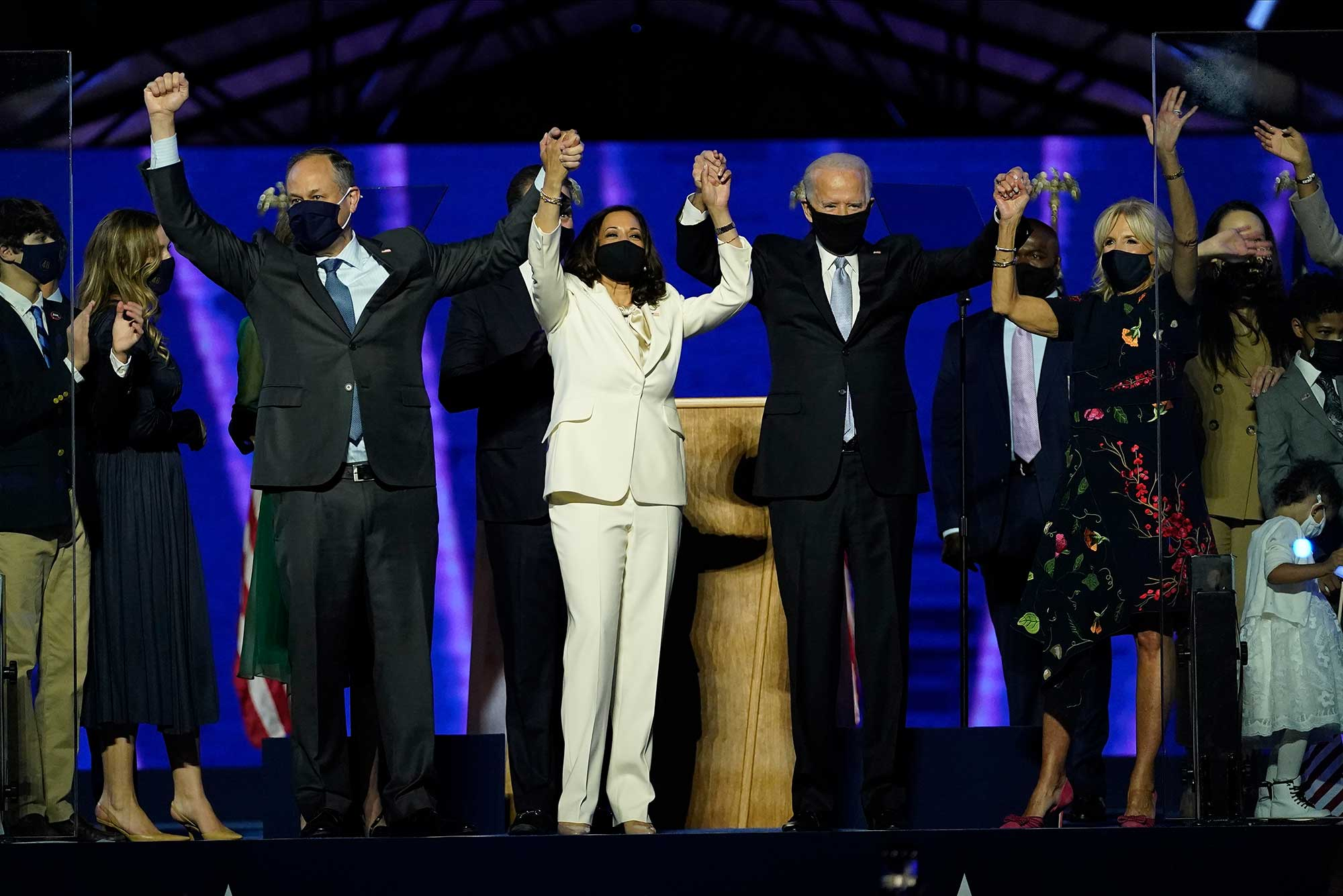 Doug Emhoff, Vice President-elect Kamala Harris, President-elect Joe Biden and his wife Jill Biden raise their hands in victory on stage together, Saturday, Nov. 7, 2020, in Wilmington, Del.