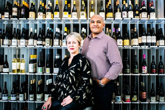 TJ and Hadley Douglas, owners of Urban Grape in Boston, pose for a photo on November 2, 2020. A floor to ceiling rack of wine bottles is seen behind them.