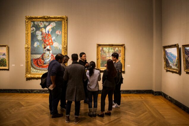 Photo of a group of students gathered in the MFA in 2018. Behind the students are two large works of art in ornate frames. A semi -circle of students listen as one student presents their work of choice.