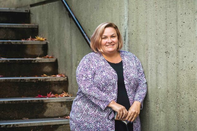 Photo of Amy Goodrich, director of catering at BU, in a colorful sweater posing at the bottom of a staircase.