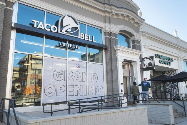 "Photo of Bostonians entering the new Taco Bell at 872 Commonwealth Ave. which has been generating big buzz among students. Photo shows the facade of store, a large gray ""GRAND OPENING"" sign is seen in the storefront windows."