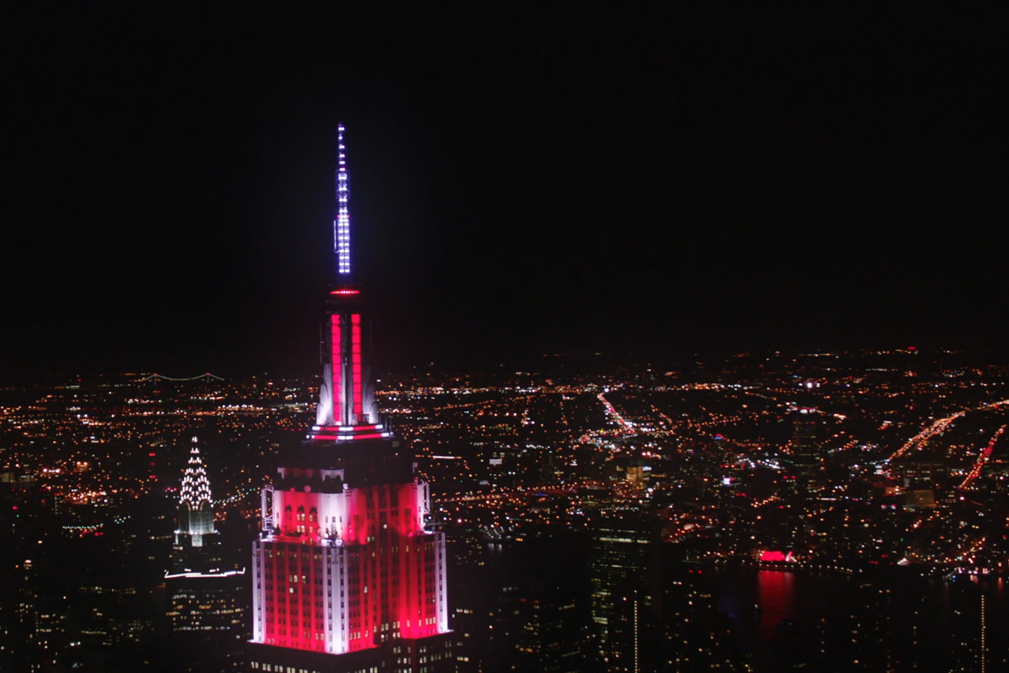 Juengling's lighting work on the Empire State Building. The skyscraper is lit up in red and white.