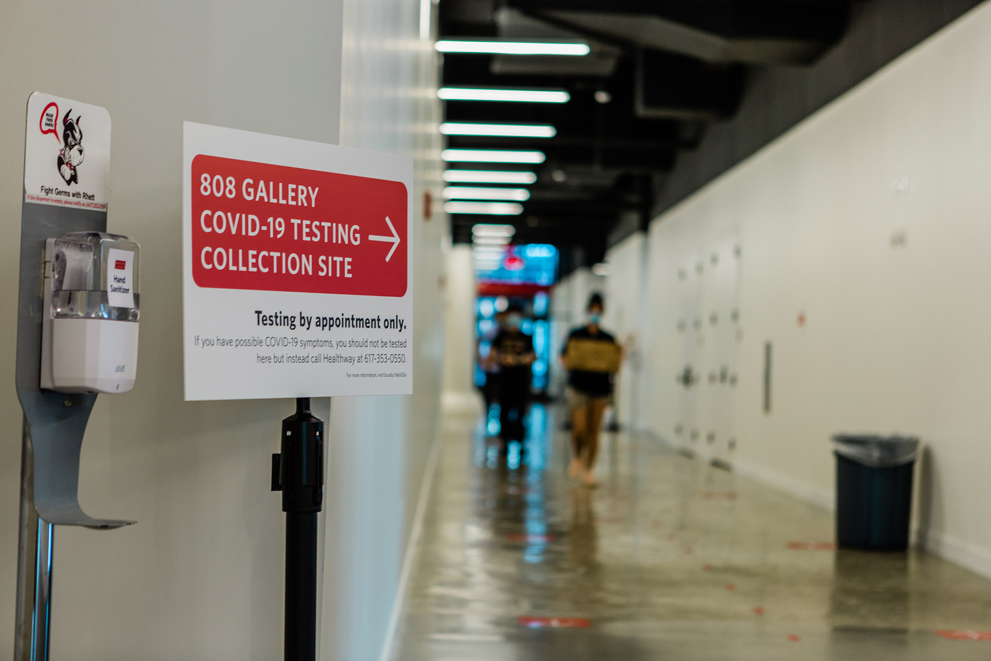 "Photo from inside the Covid-19 collection site at 808 Commonwealth Ave taken in August, 2020. A sign reads ""808 Gallery COVID-19 Testing Collection Site"" with a red arrow, below it reads ""testing by appointment only."" A hand sanitizing station is next to the sign, it has a photo of Rhett above it."
