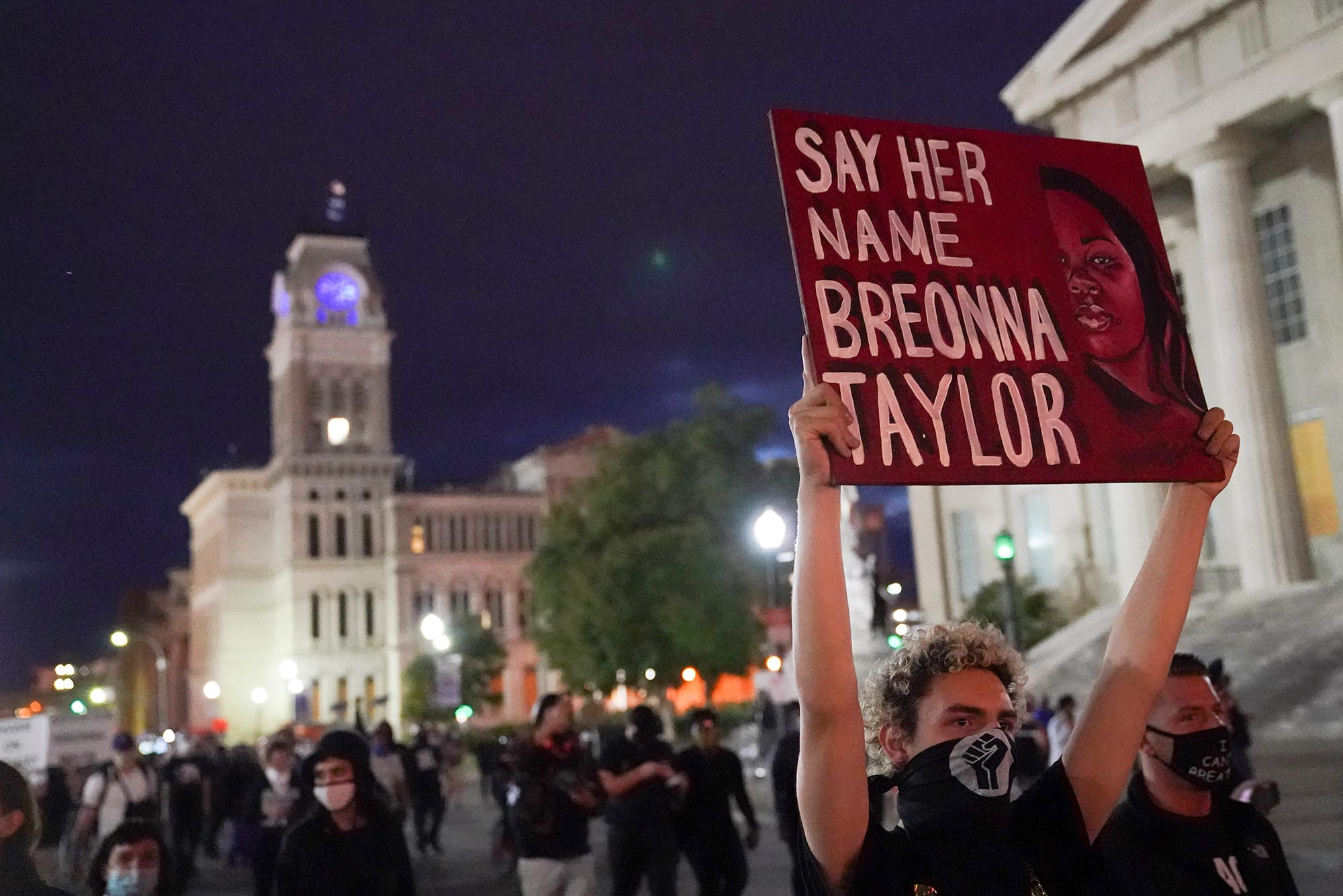 "Photo of a protestor holding a red sign that reads ""SAY HER NAME BREONNA TAYLOR"" during a September rally in Louisville, Kentucky. The protestor has a black power fist on their face mask, a crowd of people and a tall white building are seen behind them."