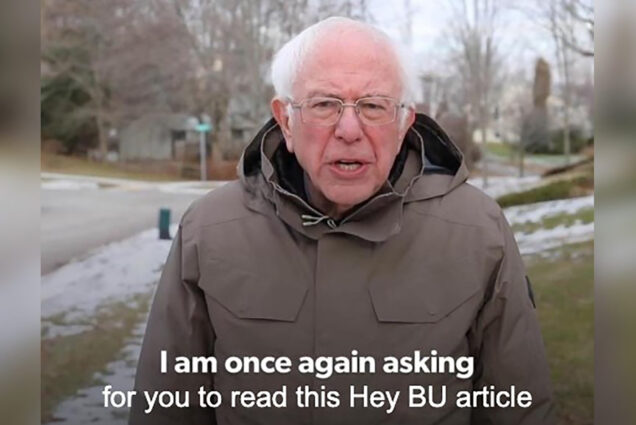 "Screenshot of Bernie Sanders in a light brown rain coat from his iconic fundraising campaign video during the 2020 presidential primary. The closed captioning text reads ""I am once again asking for you to read this Hey BU article."" Behind, a suburban neighborhood street corner is seen."