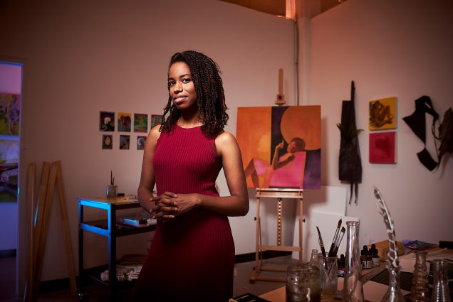 A portrait photo of Adrienne Elise Tarver standing in front of one of her paintings
