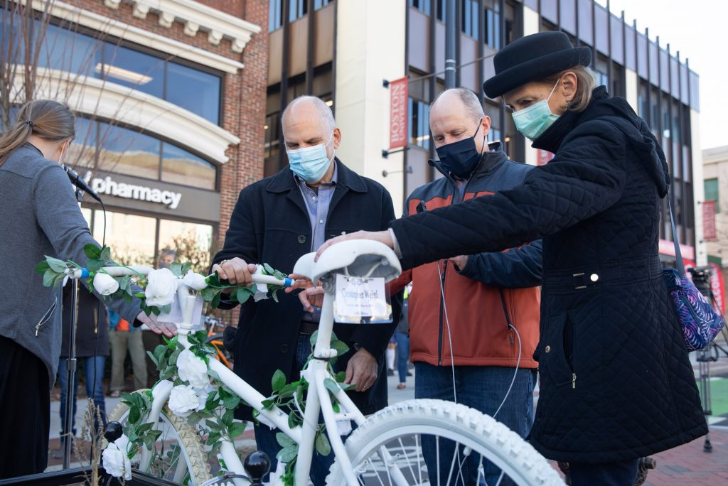 Andy Weigl, (left) and his wife Bonnie Weigl (right) pay tribute to their son Christopher's ghost bike during the Massachusetts Bicycle Coalition's memorial ghost bike installation ceremony Saturday, November 21, 2020 on the corner of Commonwealth Avenue and St. Paul Street in Boston in honor of Christopher Weigl (COM'14) who was killed by a truck driver on December 6, 2012.