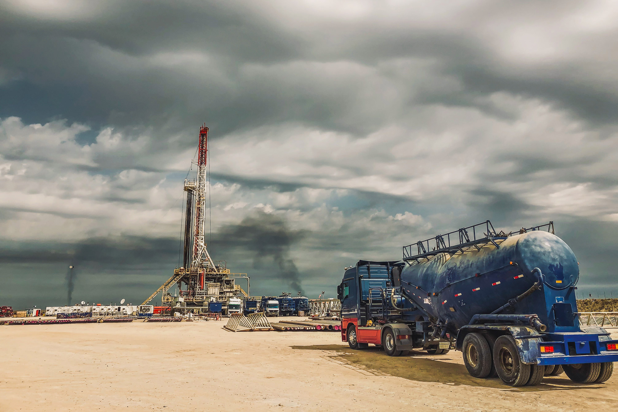 A photo of a truck approaching a fracking rig