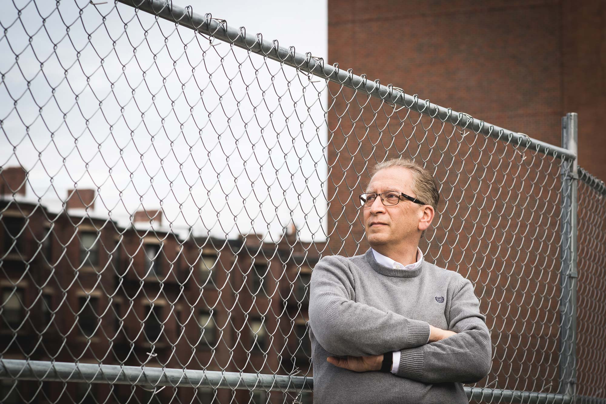 Azer Bestavros, associate provost for computing and data sciences, standing with his arms crossed in a gray sweater and looking off into the middle distance as he leans on a fence near the site of the future data sciences building.