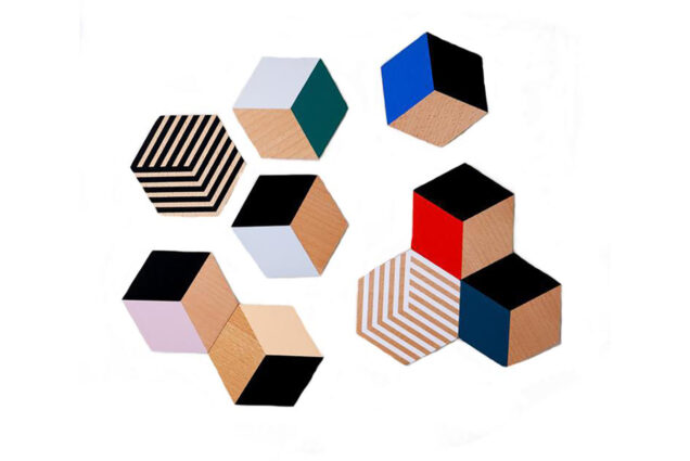Photo of table tile coasters with colorful 3-D looking cube designs on a white background.