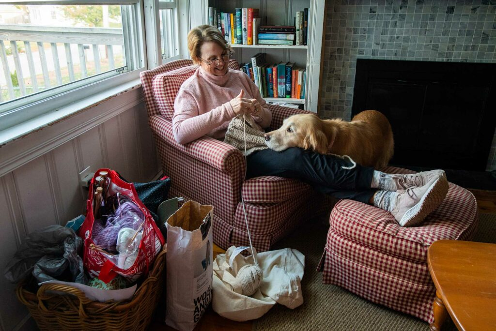 Photo of Megan Nocivelli, lecturer, administrative sciences, Metropolitan College, sitting in her home smiling with her dog on her lap as she knits. Yarn is seen in bags on the ground around her chair.