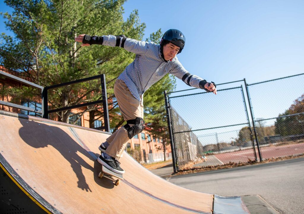 Photo of Scott Bunch, College of Engineering associate professor of mechanical engineering, materials science and engineering, skateboarding down a skate ramp with a helmet and pads while wearing khakis and a button down.
