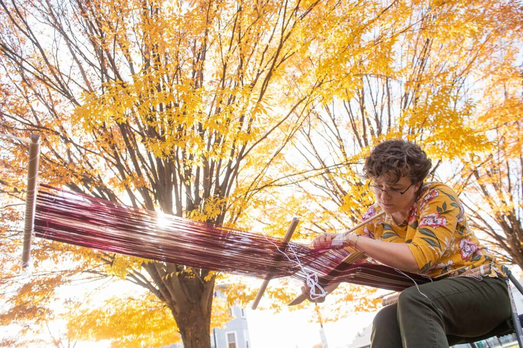 Photo of Megan Berkowitz (STH'21, SSW'21) leaning over a loom while backstrap weaving by hand. A tree with bright yellow leaves is seen in the background.
