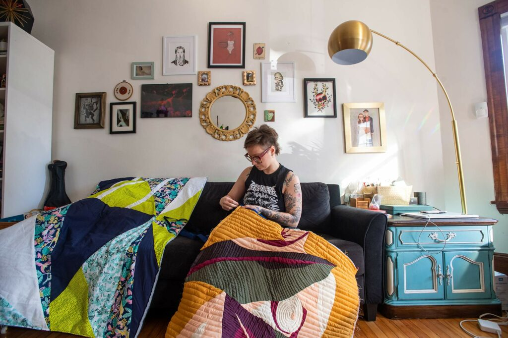 Photo of Janice Checchio, associate creative director, BU Photography sitting on her couch as she works on a large quilt with brightly-colored geometric shapes.