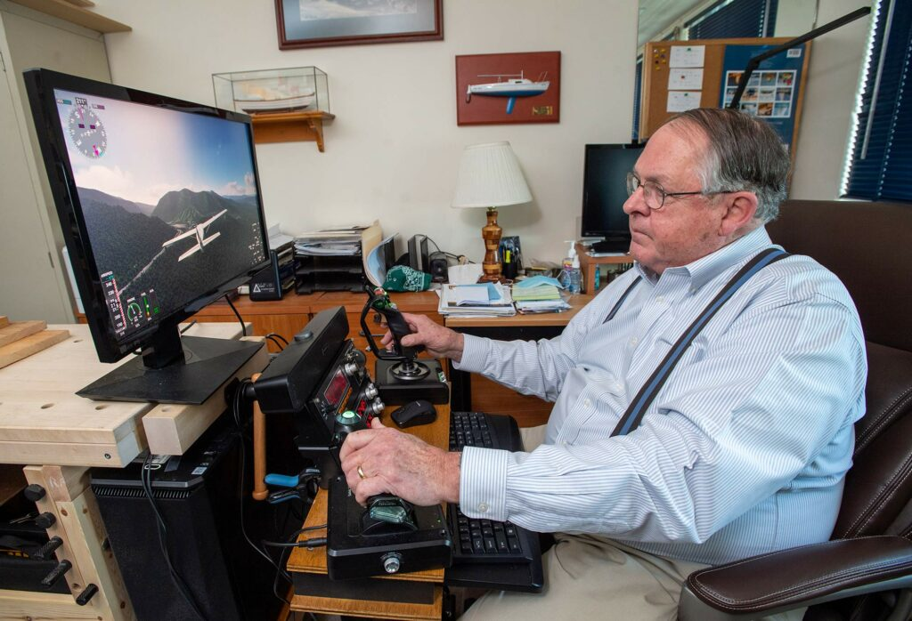 Photo of Bill Dupee, business analyst/consultant, Questrom Info Tech Services Department, sitting in front of his computer as uses different joysticks to fly a plane using a flight simulator he built with his son.