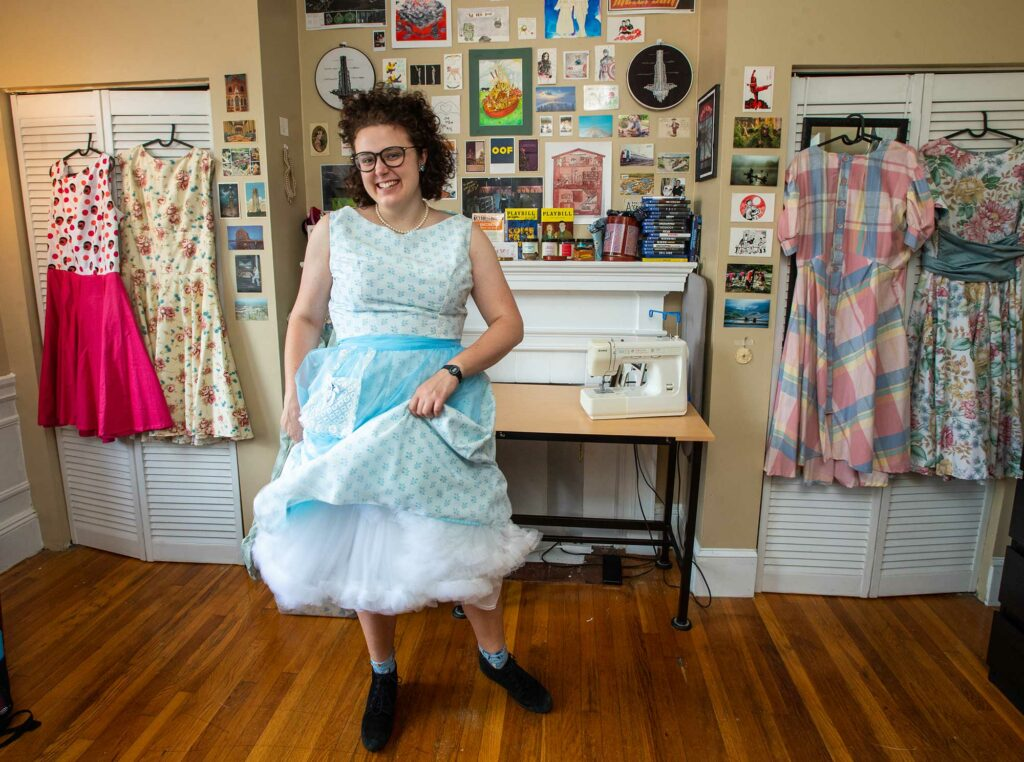 Photo of Grace Saathoff, here in her Brookline home, sewed a wardrobe of vintage-inspired dresses over the summer. Saathoff wears a light blue polka-dotted dress and smiles; other dresses she's made hang in the background.