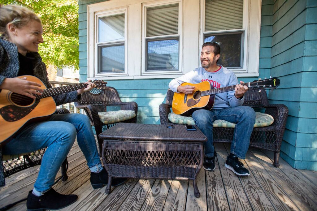 Photo of Thomas Bohrer plays some guitar with his daughter Sabrina at her home in Somerville.They sit outside on the porch of a light blue house.