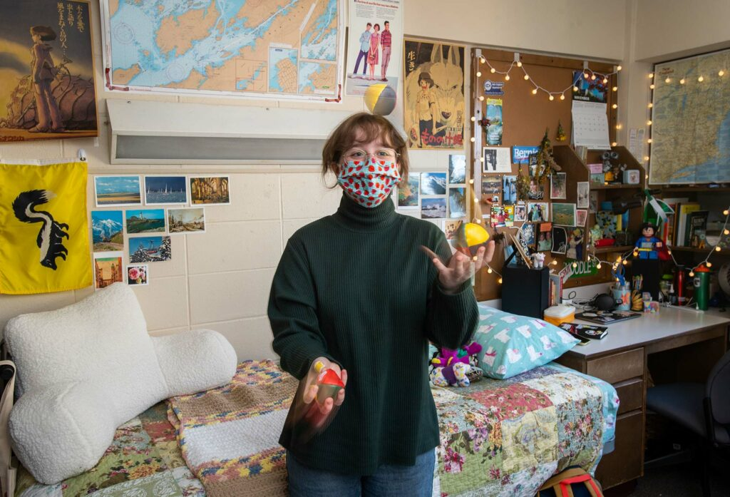Emma French in her Warren Towers dorm room practicing her juggling. She wears a spotted face mask; her dorm walls are covered with maps, photos, and cork boards.