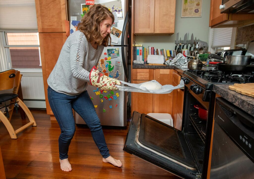 Photo of Katherine Meyer Moran with one of her loaves of sourdough bread at her home in Brookline. The oven is open as she quickly goes to slide in the bread. A fridge with fridge magnets are seen in the background.