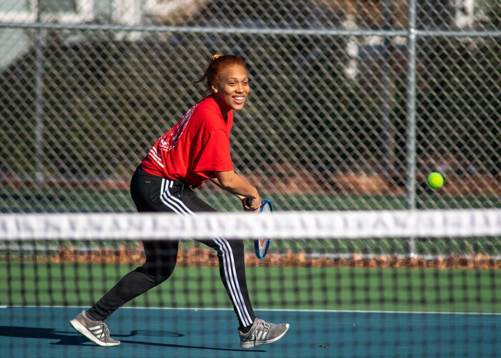 Photo of Nyah Jordan, BU Student Government vice president for internal affairs, in a red shirt and track paints, smiling, at the Harris Playground courts in Medford.