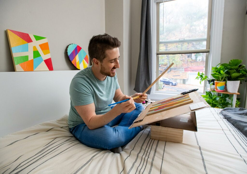 Photo of RJ Foley IV sitting on his bed working on his colorful wood art paintings in his Brighton home, with completed pieces behind him. Bright geometric shapes are seen on a circular and square piece of wood.