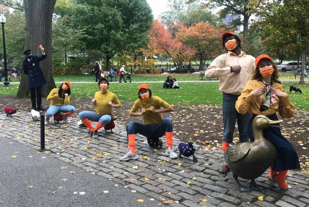 A photo of cast members sitting on the Make Way for Ducklings sculpture in the Boston Public Garden