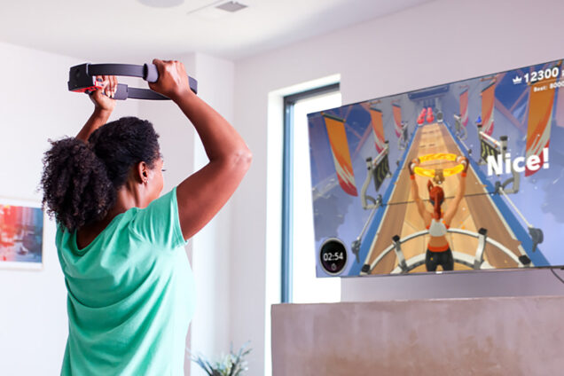 Photo of a woman working out while the Nintendo Switch game Ring Fit Adventure plays on the TV. The TV screen shows an avatar with the ring and words 'Nice!'