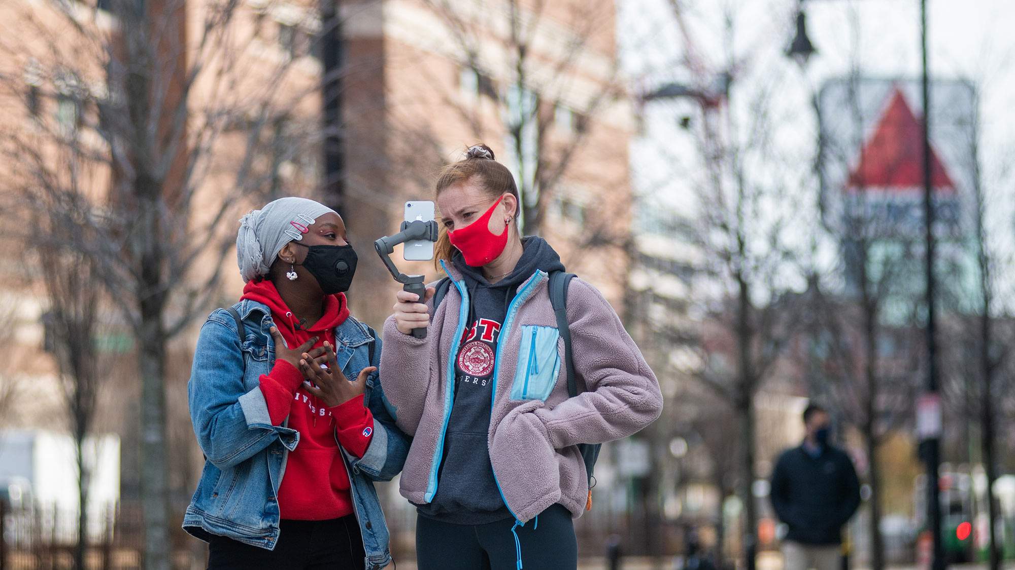 Photo of Hikima Lukomwa (SAR'22), community linked coordinator, in a red sweatshirt and jean jacket, with Jillian White (COM'22), in a pink fleece, a community development leader, while they give a virtual tour use a handheld phone tripod. The Citgo sign is seen blurred in the background.