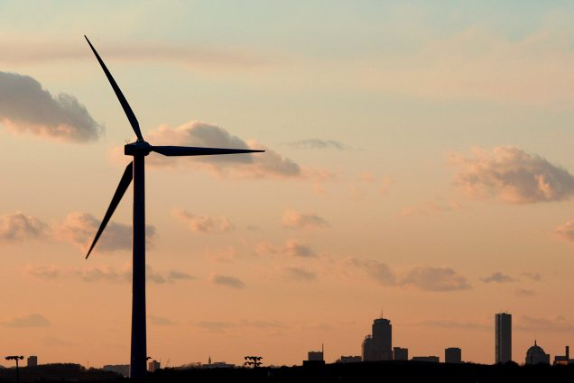 A photo of a wind turbine in front of Boston's skyline