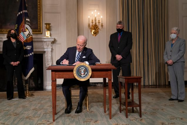 A photo of Joe Biden signing climate legislation at a desk in front of Vice President Kamala Harris and another administration officials