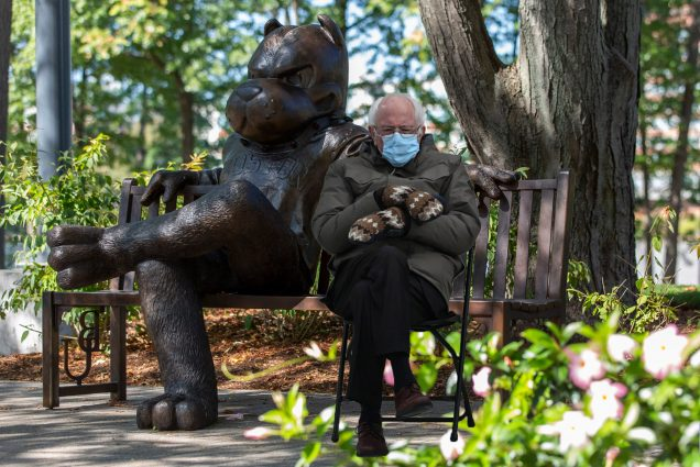 A photo of Bernie Sanders sitting with mittens and a jacket on next to the statue of Rhett on a bench on BU Beach.