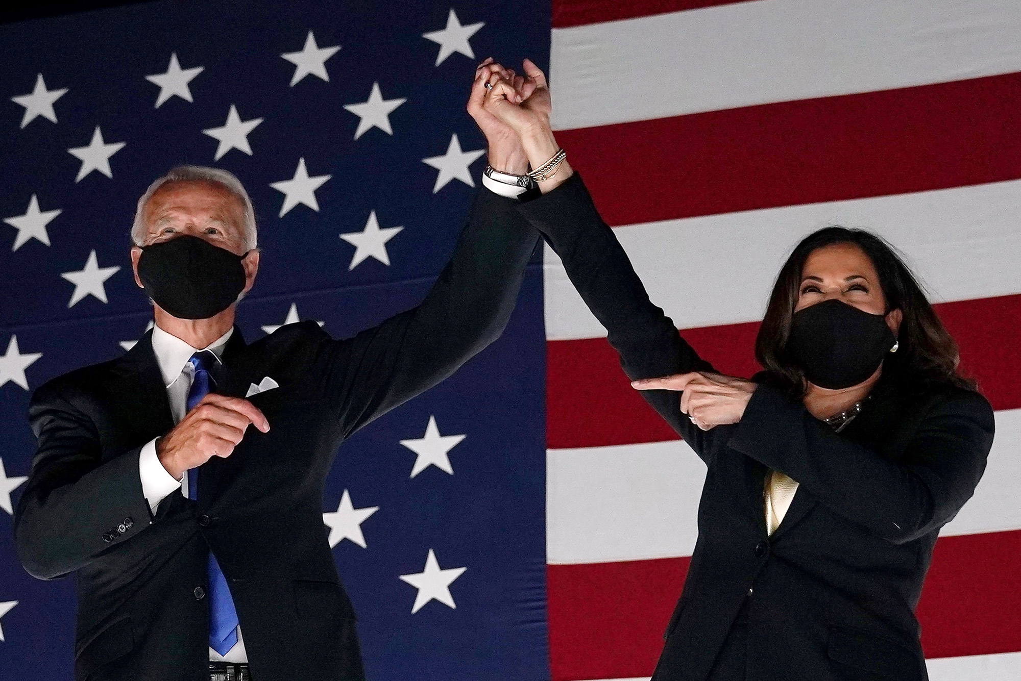 A photo of president-elect Joe Biden and Vice President-elect Kamala Harris clasping hands and raising them above their heads. They are standing in front of an American flag. Both are wearing masks.