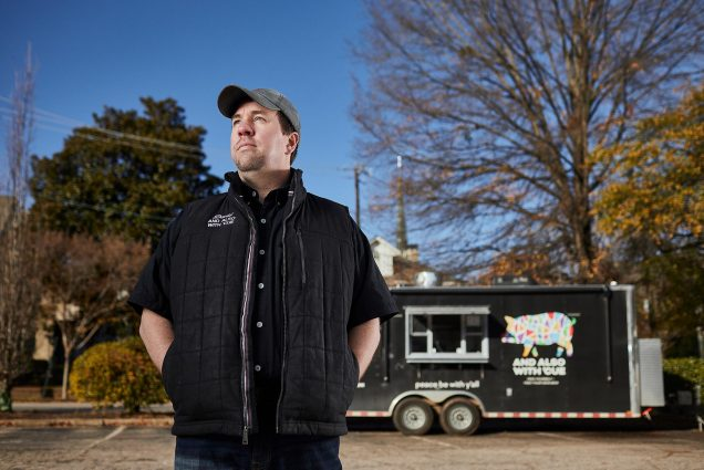 Photo of David With in a black vest, shirt, and baseball cap, standing with his hands in his pockets and looking off to the side. His the black trailer where he runs his BBQ business out of is behind him; blue sky and trees are seen in the background.