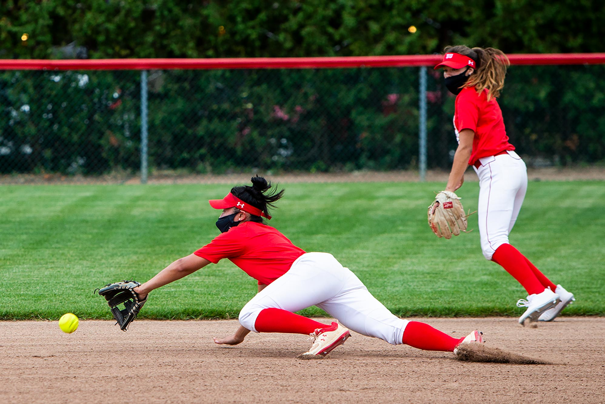 Photo of two of BU softball players, both wearing black masks and red and white uniforms. One woman lunges to the ground to field the ball while another backs her up.