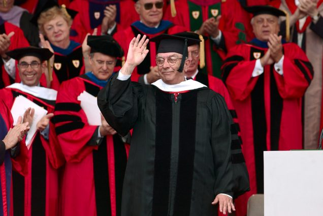 Photo of Jon Westling receiving an honorary Doctor of Humane Letters Degree in 2003. Westling wears a black robe and cap and waves with his right hand. A crowd of faculty in red regalia are seen behind him.