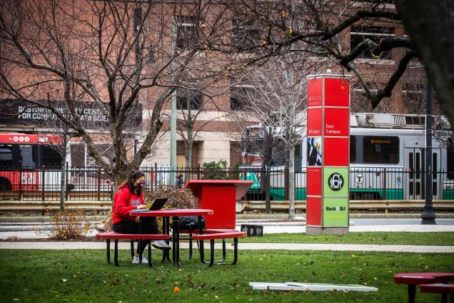 "A young female student in a red sweatshirt and black face mask sits by herself at a red picnic table on a lawn on BU's Campus. A signpost behind her reads ""Back2BU""; the green line and a BU shuttle bus drive by in the background. The trees are bare."