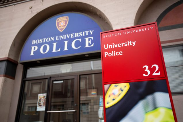 "Photo of the entrance of the Boston University Police building, its name written on a blue arched sign above the doorway. A red sign that reads ""University police"" with a larger number 3 is seen in the foreground."