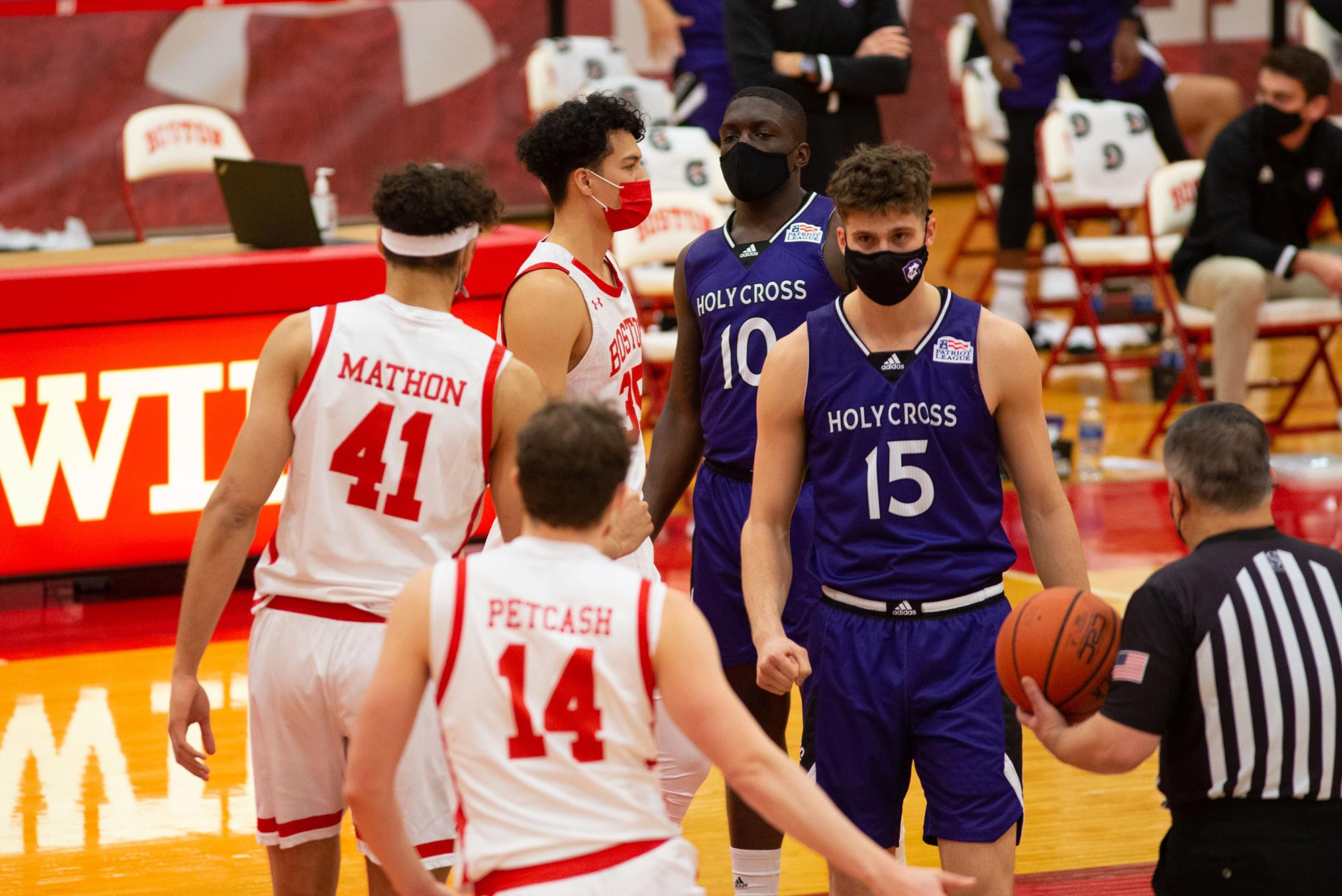 Photo of BU and Holy Cross men's basketball players walking by one another during the pre-game of one of their opening season games. Each of young men wear a face mask, and a referee with a ball in his hands is seen in the foreground.