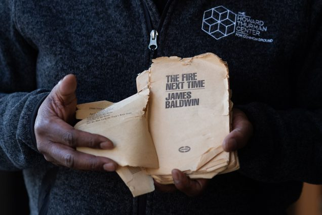 "Photo of Dean Elmore holding a tattered copy of ""The Fire Next Time by James Baldwin. The photo is a tight shot on Elmore's hands as he opens to the book's yellowed title page."