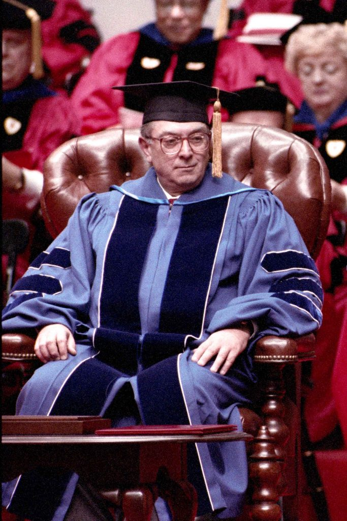 Photo of the Inauguration of Jon Westling as the President of Boston University in October 1996. He sits in a large, leather chair in light blue and dark blue regalia.