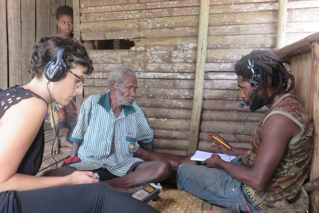 Photo of Kate Lindsey recording and listening to two people in Papua New Guinea as they speak. A small child looks on from the door way. Lindsey wears headphones and looks down at a recorder as her subject speaks into the microphone of a headset.