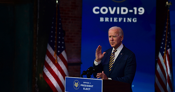 "Photo from December 29, 2020 of U.S. President-elect Joe Biden delivering remarks on the ongoing coronavirus (COVID-19) pandemic at the Queen Theater on December 29, 2020 in Wilmington, Delaware. Biden stands behind a podium that reads ""Office of the President Elect,"" his hand raised. Behind him, the words ""COVID-19 Briefing"" are in a white on a blue background."