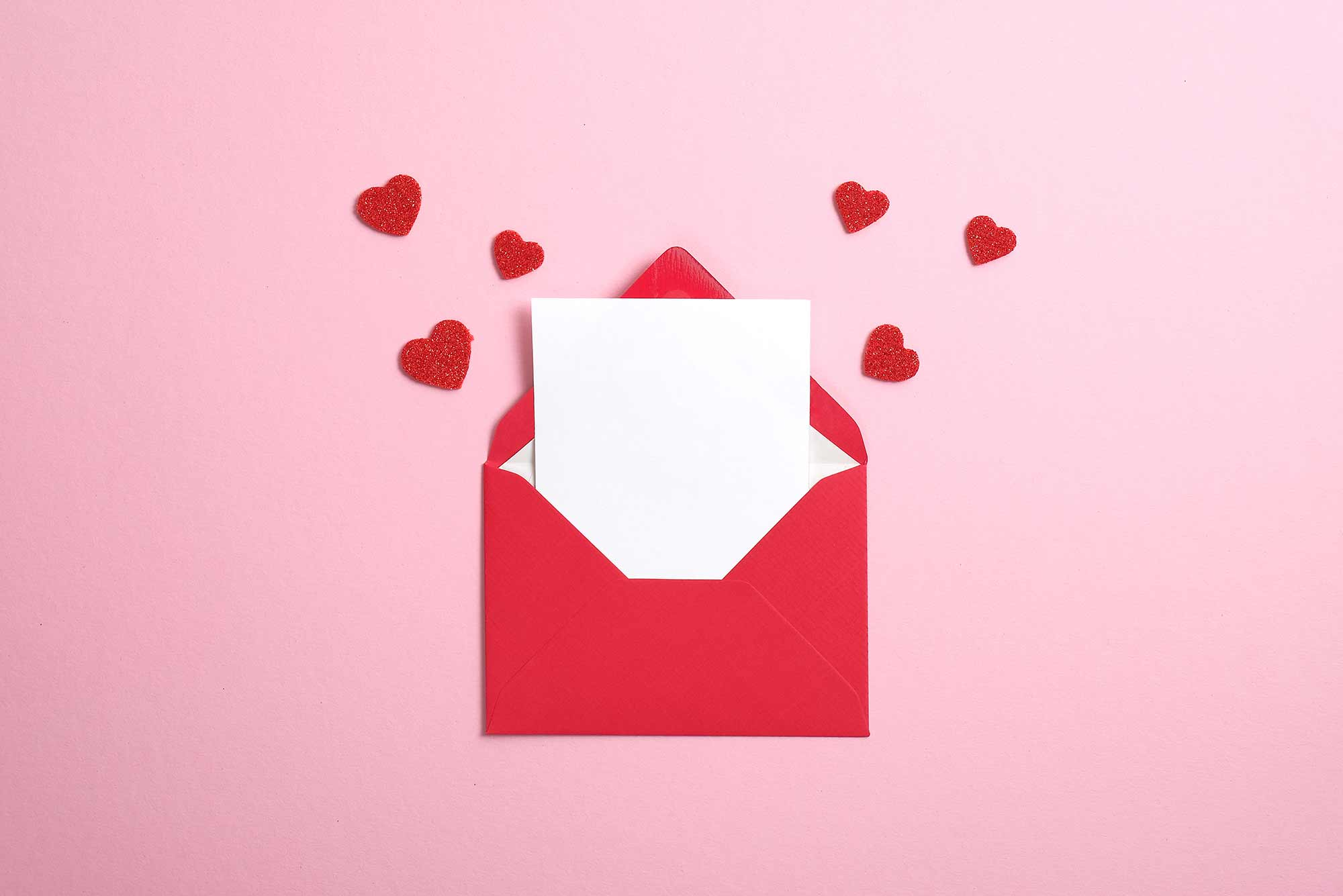 Blank Valentine's Day card in red paper envelope with blank white note mockup inside and Valentines hearts on pink background.