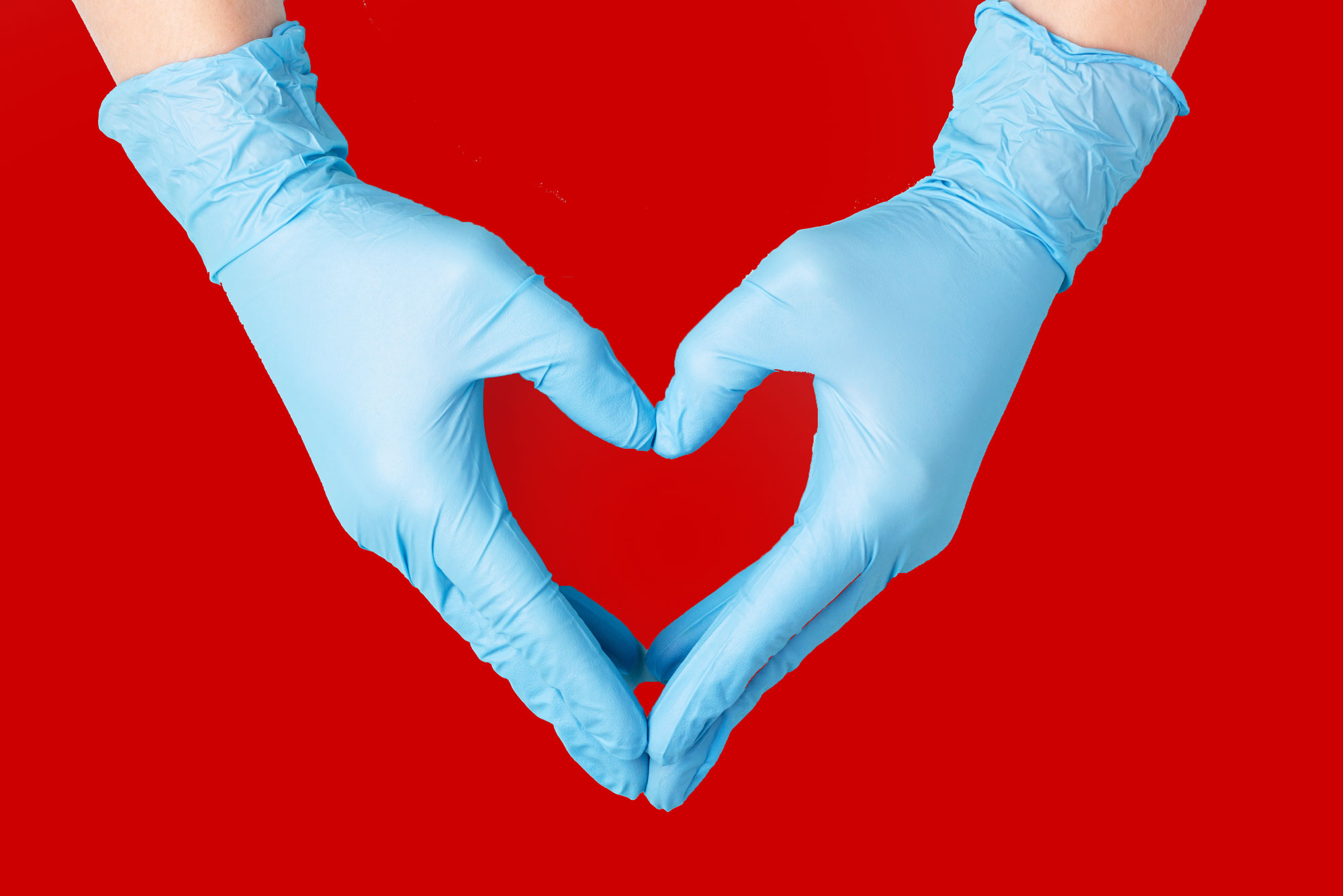 A pair of gloved hands making a heart over a red background